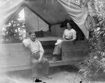 YMCA boy's camp on Orcas island showing adult man and woman seated in platform tent, 1910
